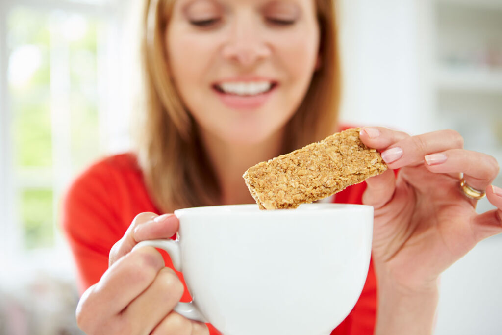 A woman dunking a biscuit into a large cup of tea