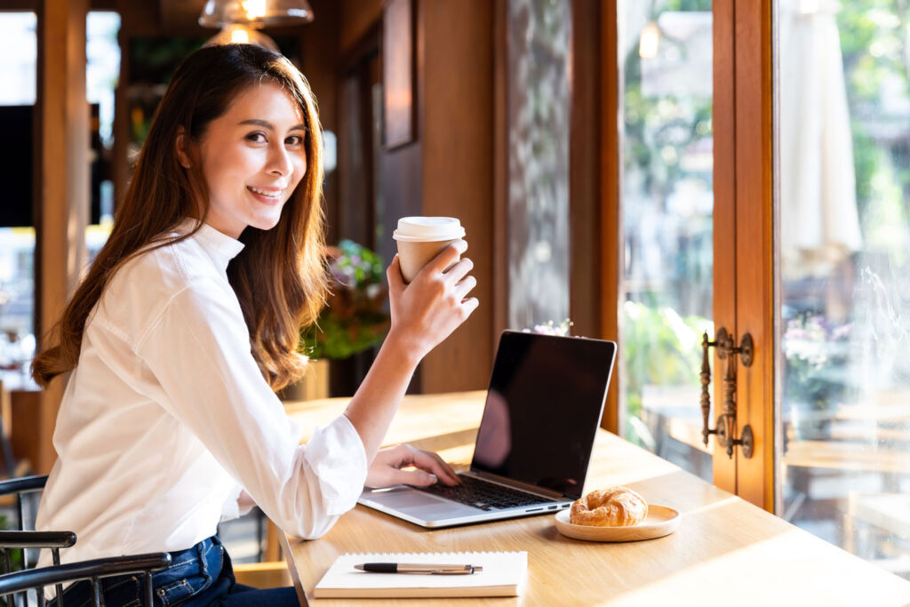 WOman holding a specialty cup of coffee in her office