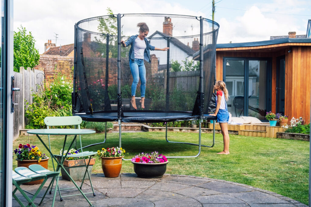 Woman jumping on a Plum Play trampoline in her garden