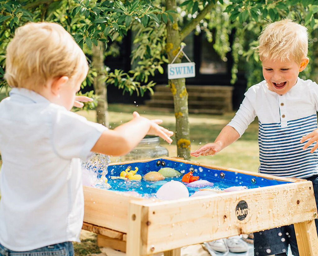 Young boys playing with toys in the water