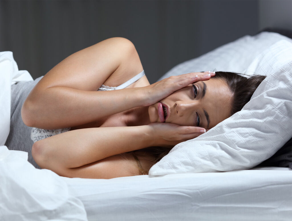 A young woman struggling to get to sleep on a hot night
