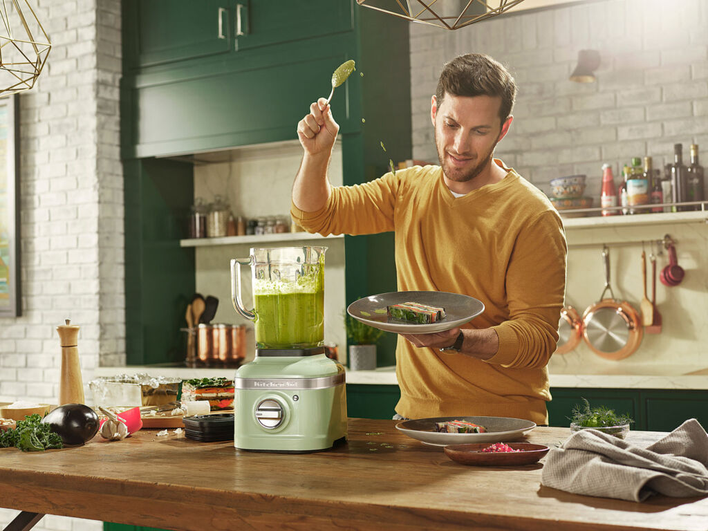 A man putting the Artisan blender through its paces in the kitchen