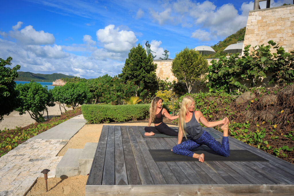 Two female guests engaging in some Yoga on the terrace
