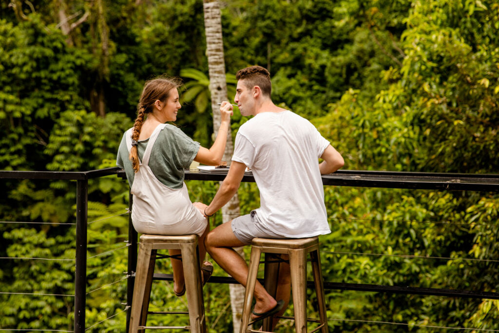 A couple sharing some cake overlooking the lush foliage