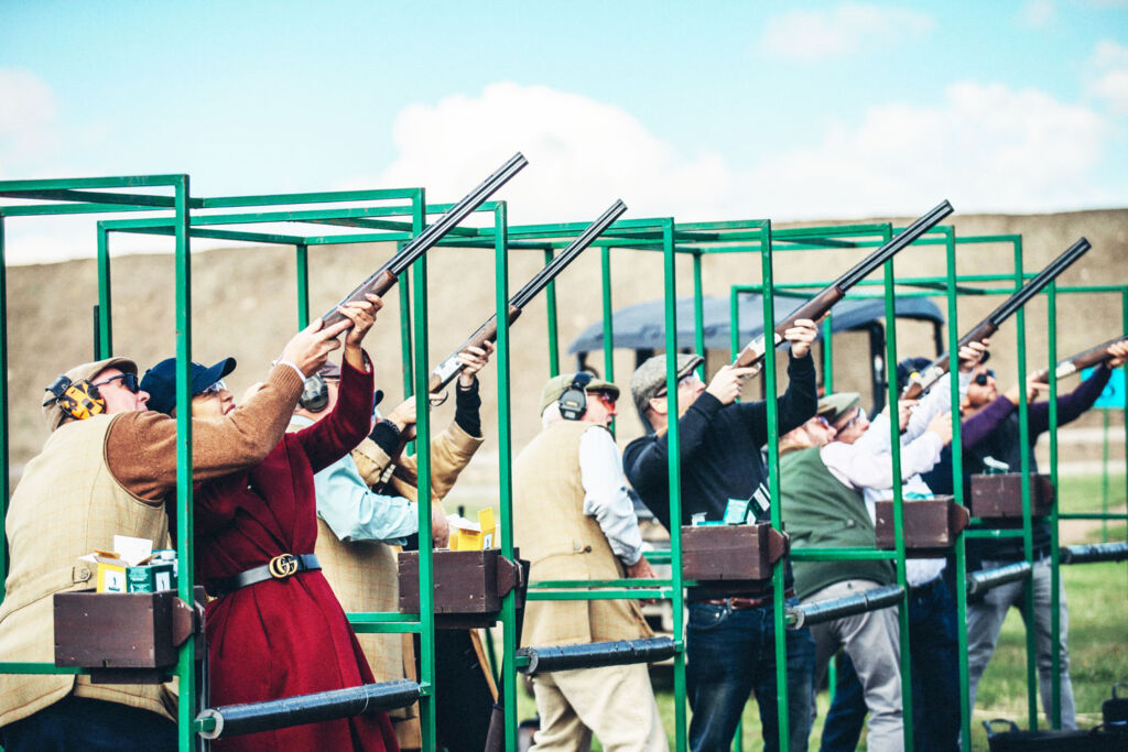 A group of men and women enjoying some clay pigeon shooting