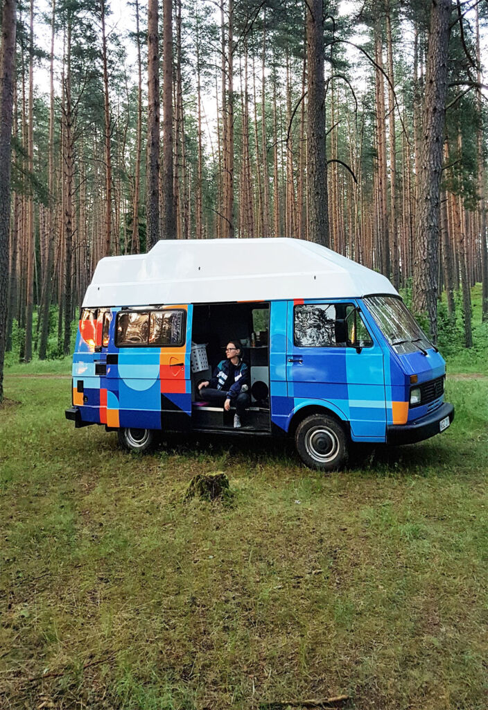 Someone enjoying the peace of a forest sat in a recreational vehicle