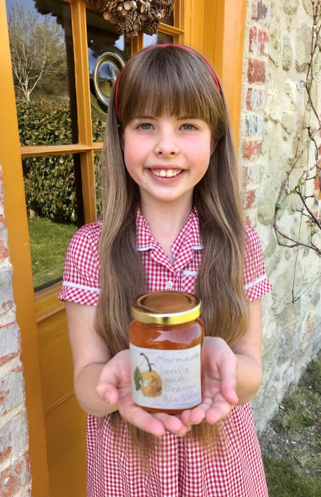 Flora holding a jar of her award-winning marmalade