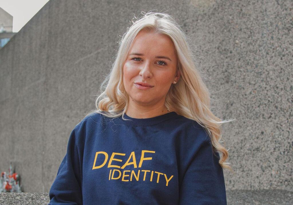 Jasmine wearing a blue Deaf Identity top