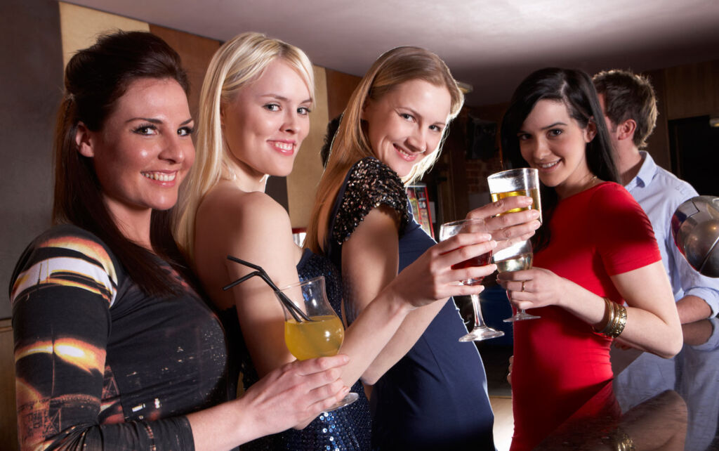 Some young ladies enjoying a few drinks at a party