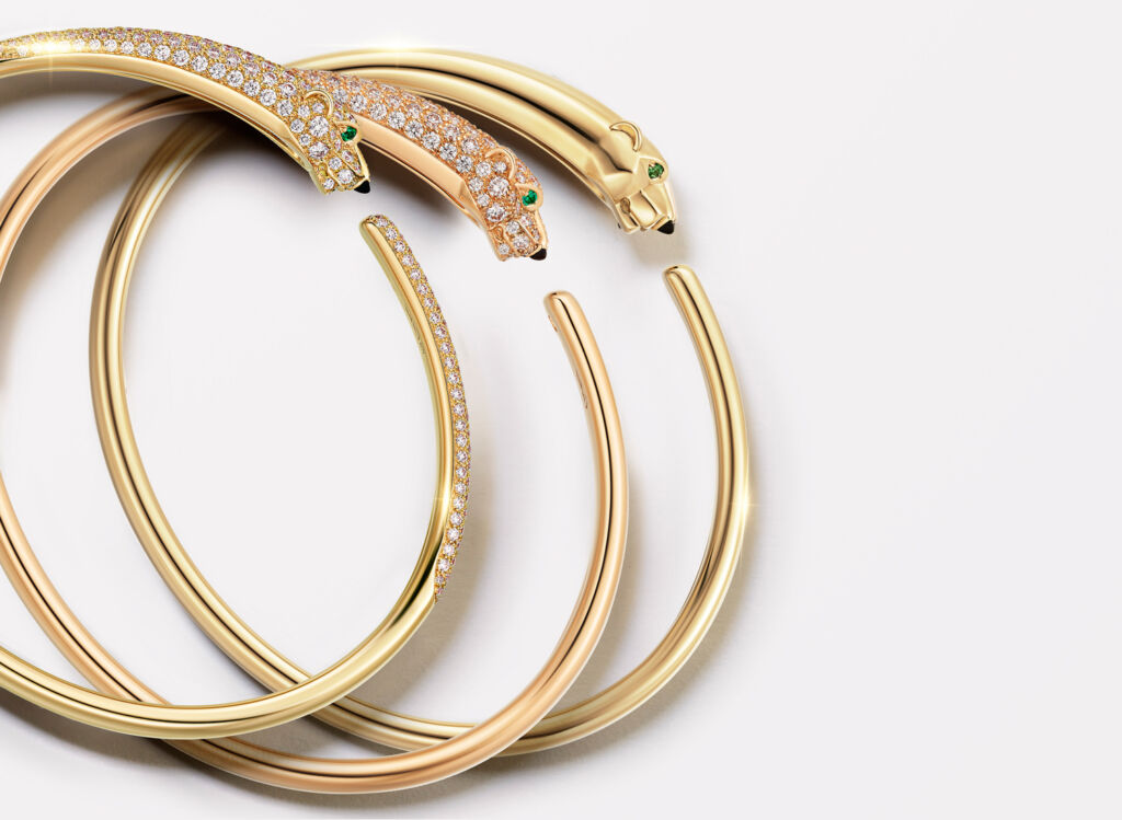 Three versions of the Cartier Panthére bracelets laid on top of each other