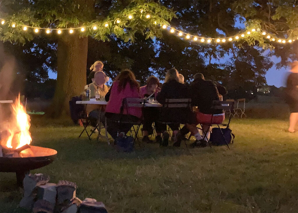 A family enjoying an meal outside in the darkness