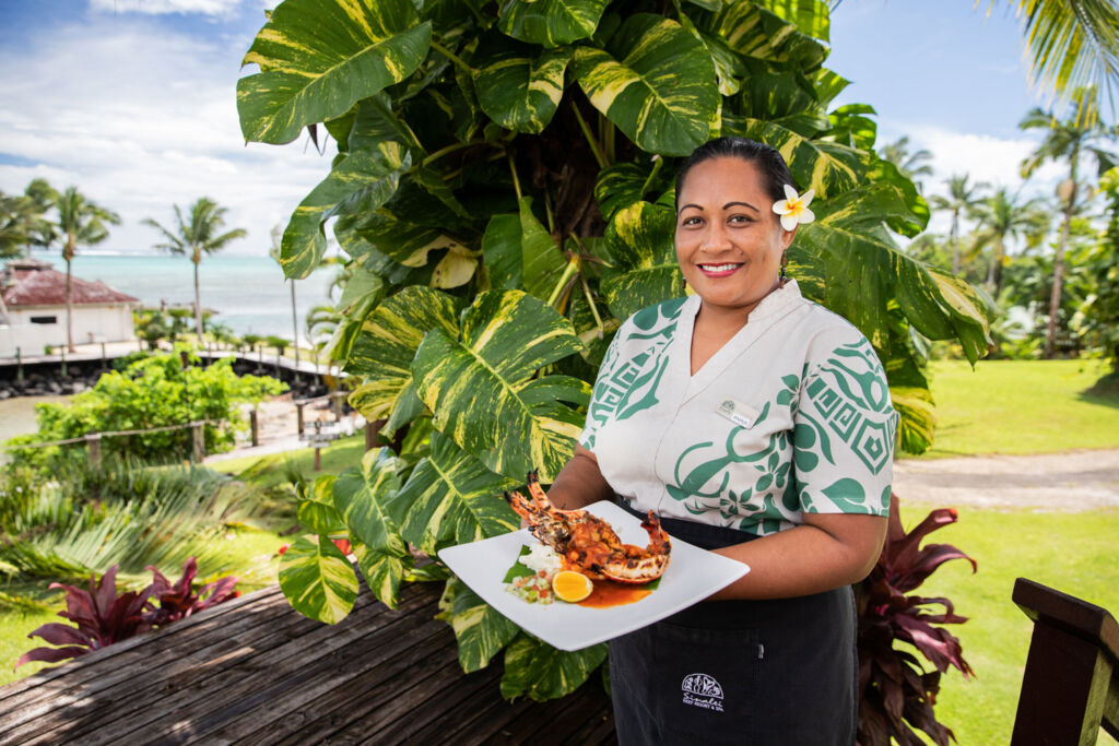 A waitress serving lobster at Sinalei Resort in Samoa