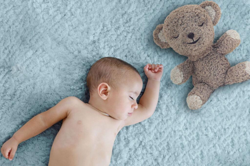A baby lying next to a SNOO Bear