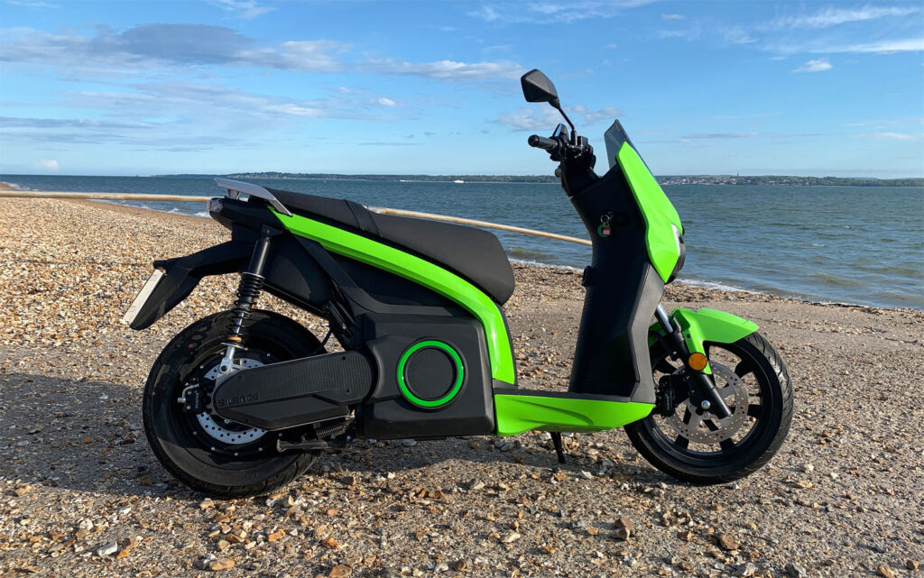 A side view of the electric scooter parked on an English beach