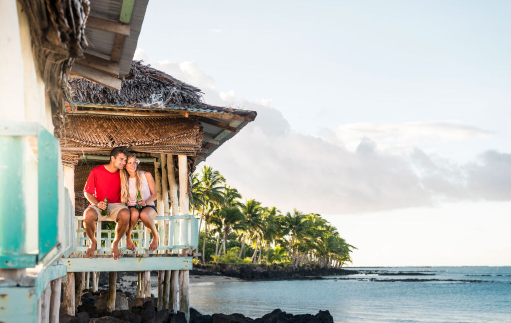 Couple sitting in a Fale on the beachfront