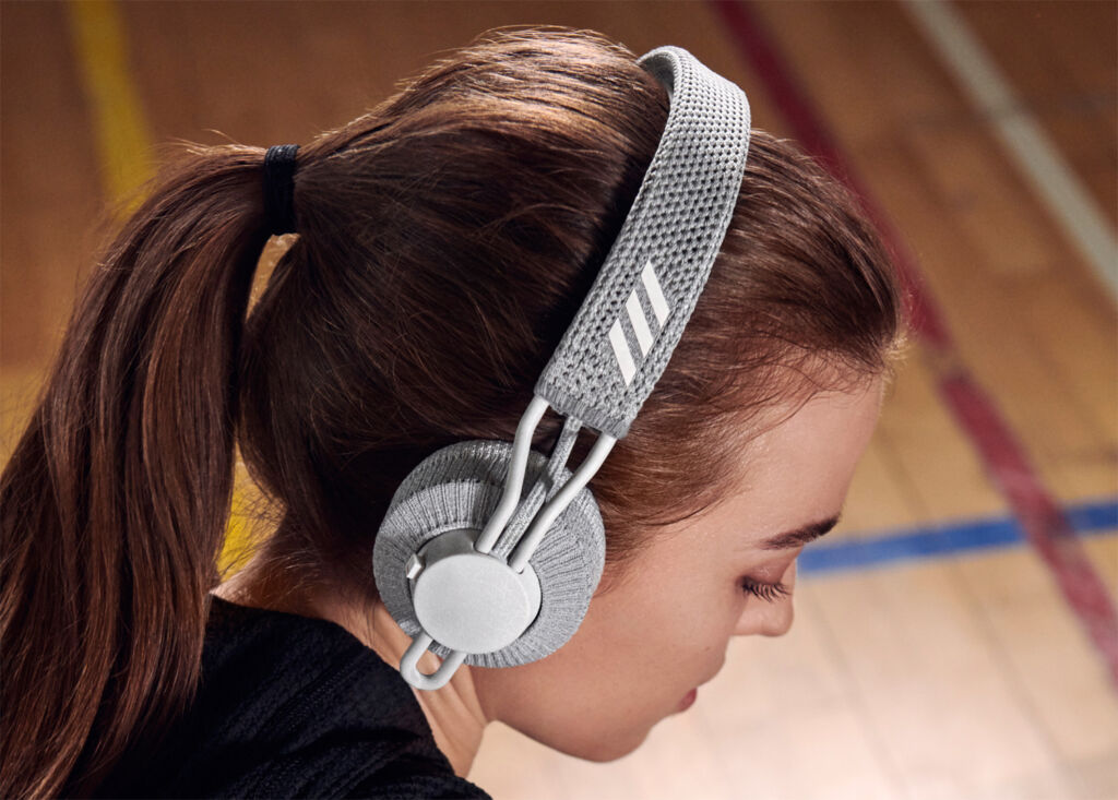 A woman wearing the headphones in a gym