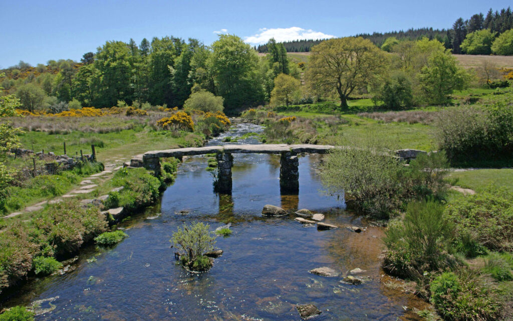 A beautiful view up a river in the countryside towards a bridge