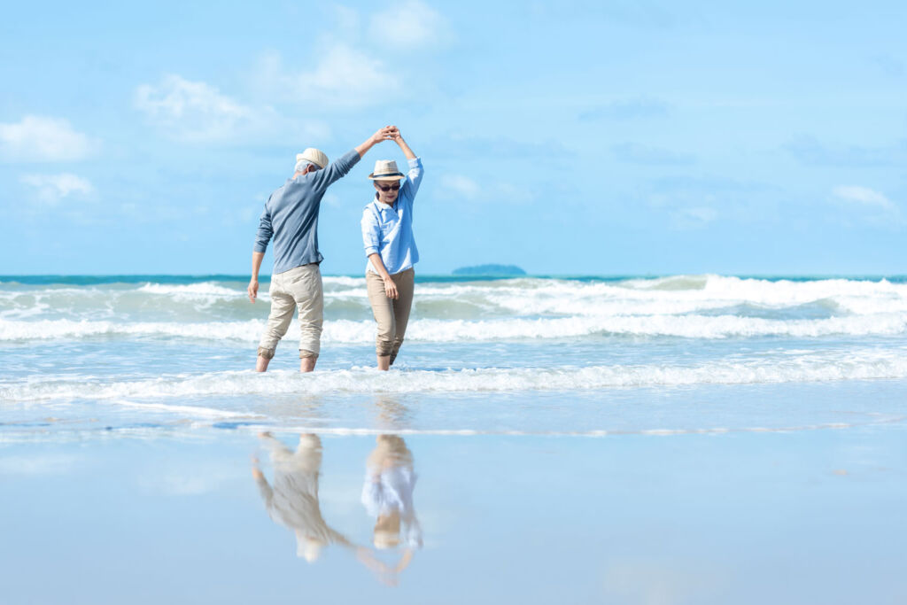 An older couple enjoying themselves standing in the shallows at the seashore