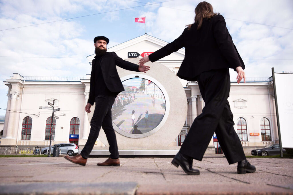 Two people reaching out to each other next to the portal