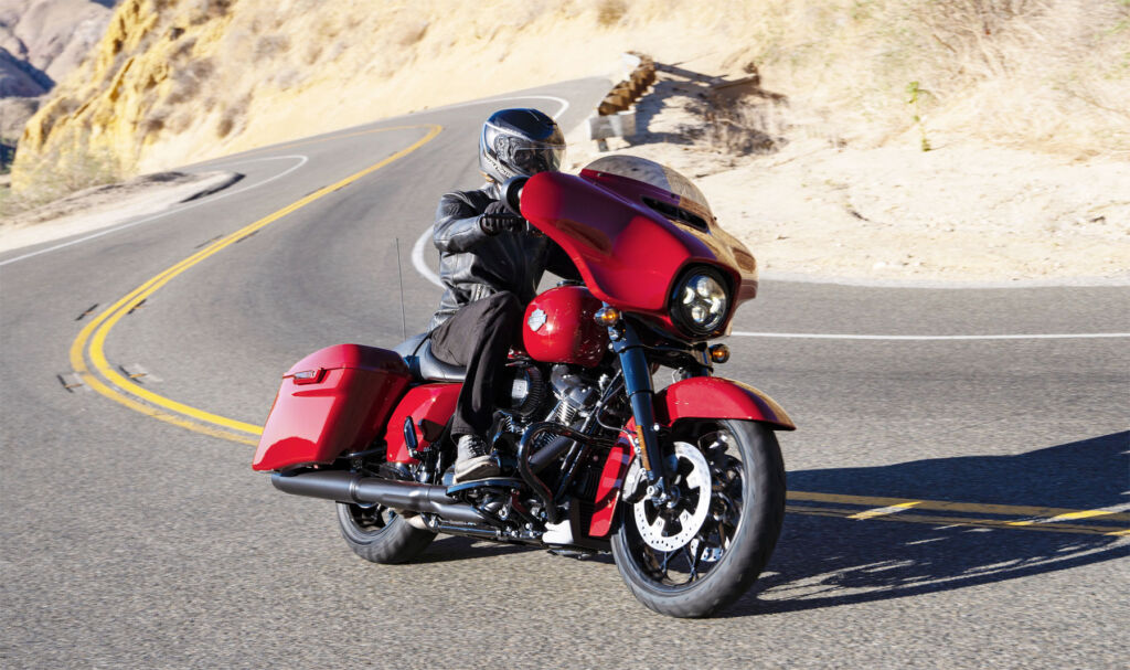 A 2021 Harley-Davidson Street Glide Special in red taking a corner on an American road