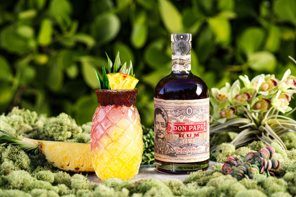 A bottle of Don Papa Rum with a Pineapple cocktail on a table