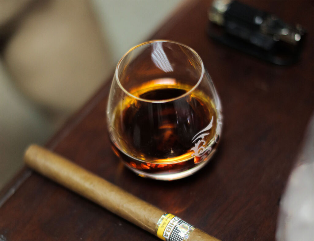 A glass of the Tributo 2021 next to a cigar