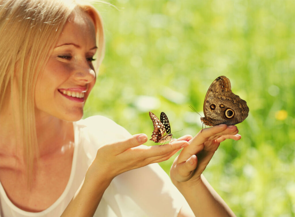 A woman letting two butterflies to rest in her hands