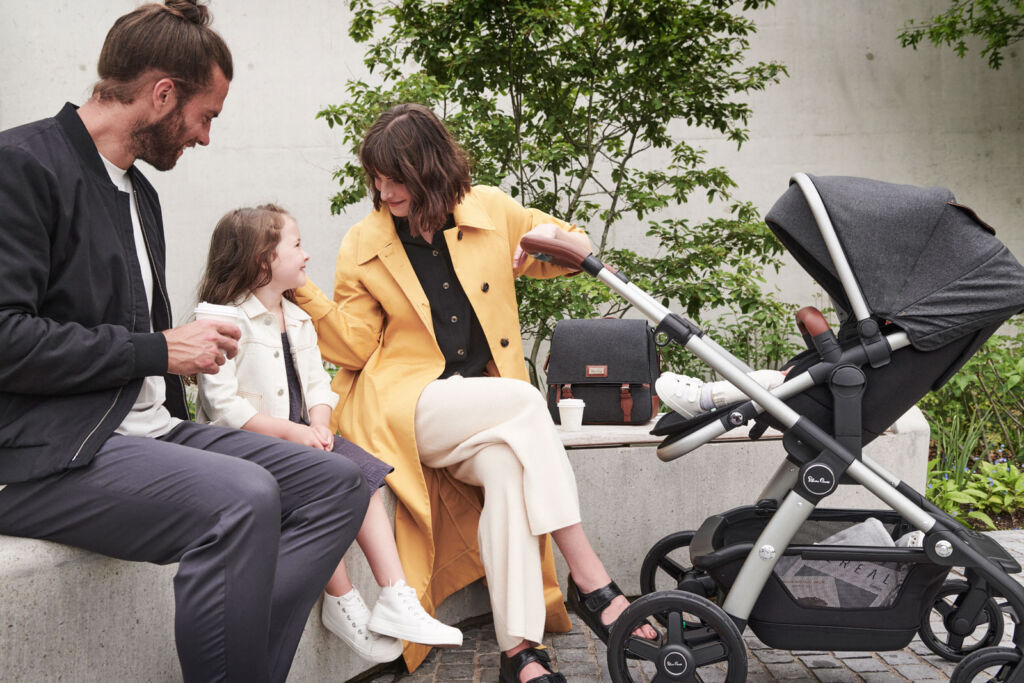 A young family outdoors with their Silver Cross pram