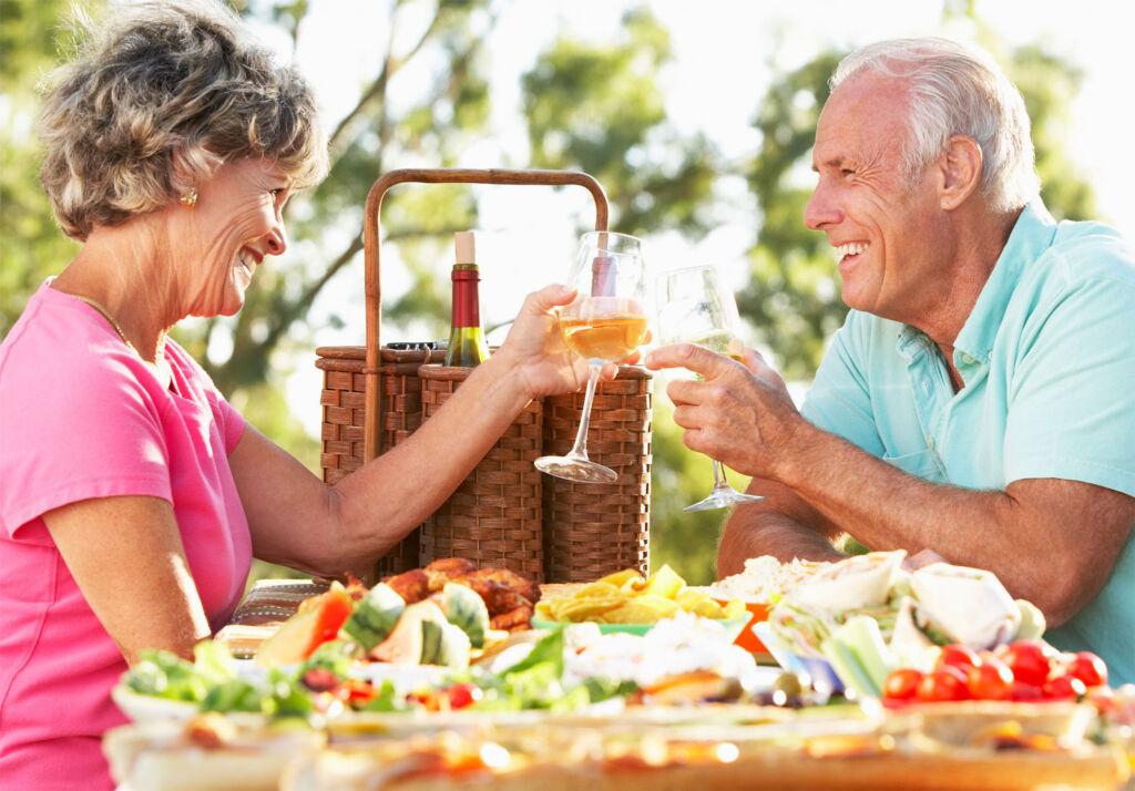 A couple having a picnic at a table in their garden