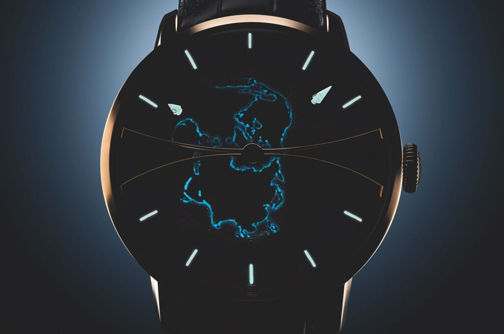The dial of the watch at night showing the outlines of the coastline via the Super-LumiNova