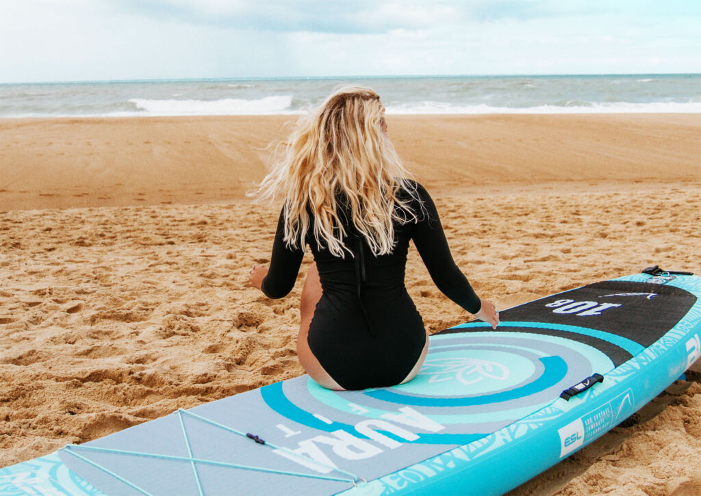 A woman sat on the Bluefin paddleboard looking out to sea