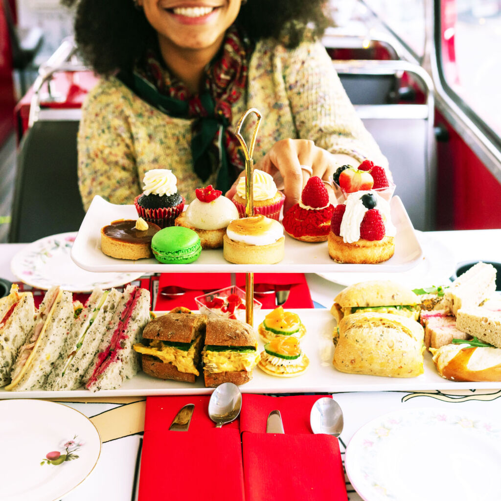 A female guest enjoying some of the food on the top deck of the Routemaster bus