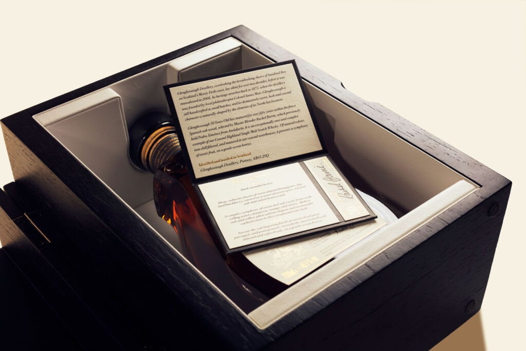 A bottle in its case with documentation including tasting notes