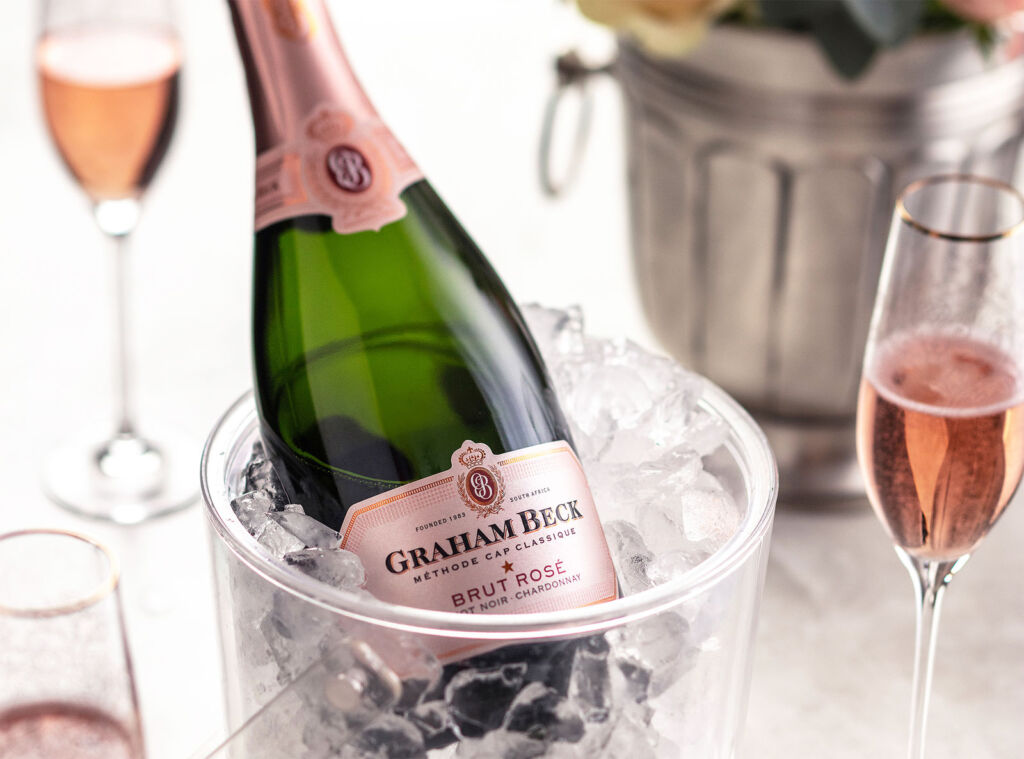 A bottle of Graham Beck Brut Rosé NV Pinot Noir/Chardonnay 12% in an ice bucket on a table