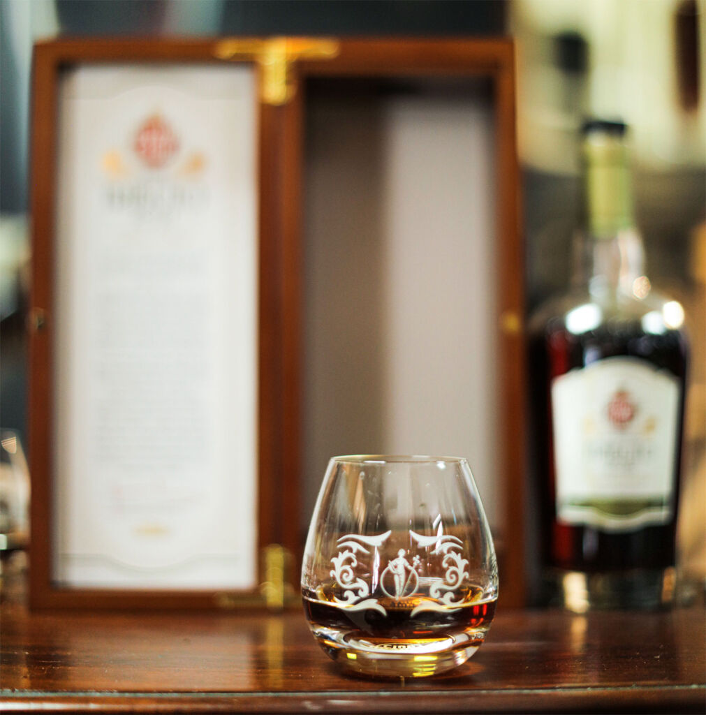 A glass of the Tributo 2021 in front of the wooden case and bottle