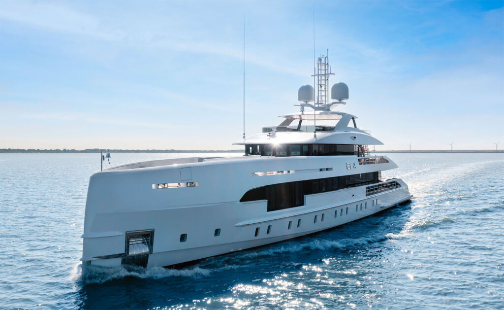The superyacht running at sea on a bright sunny day with blue skies