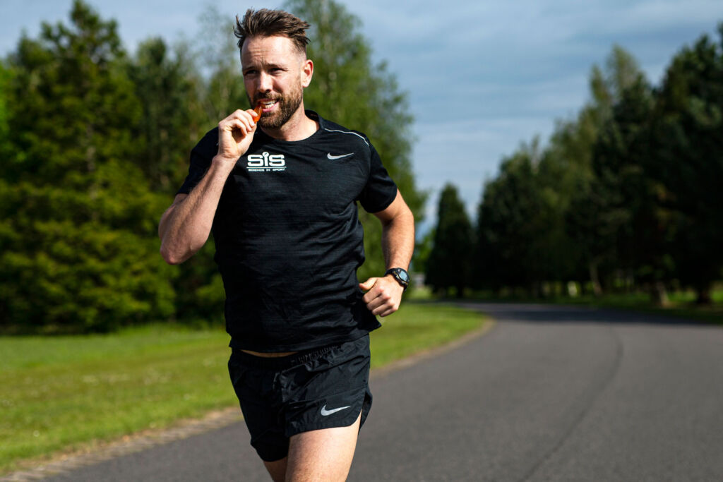 A man taking in nutrition whilst on a training run