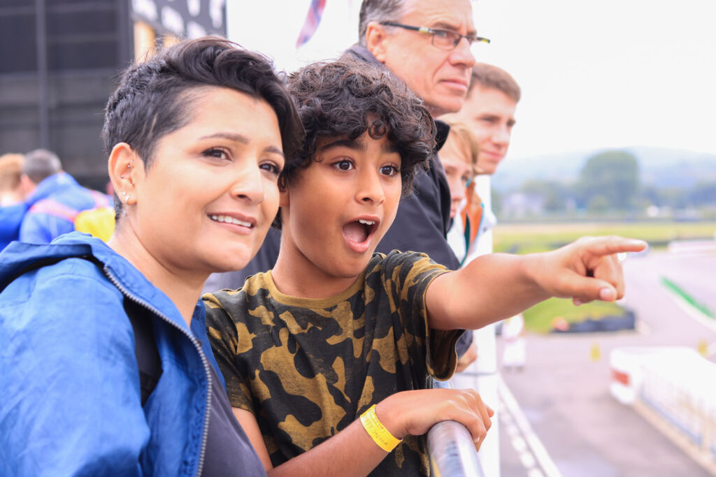 An excited young fan watching the action on the Goodwood circuit