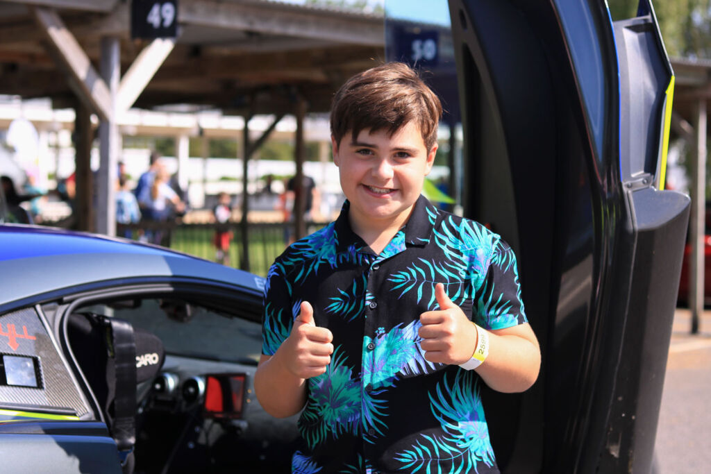 Two thumbs up from a young man at the Children's Trust Supercar Event at Goodwood