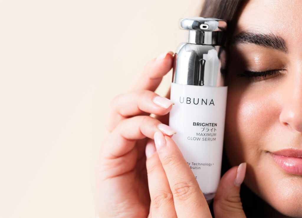 A woman holding one of the brand's beauty products close to her face