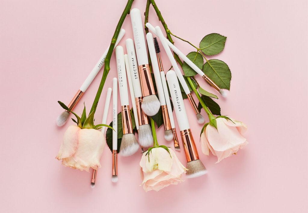 White Spectrum make up brushes alongside white roses