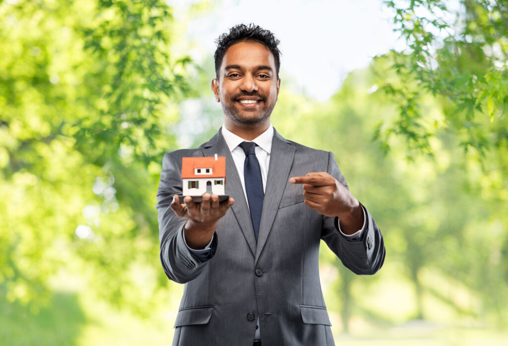 A happy real estate agent pointing to a model of the house you've given him to sell