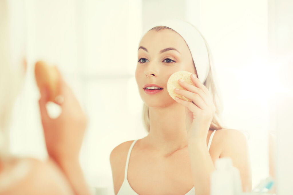 Young woman in the bathroom exfoliating her skin
