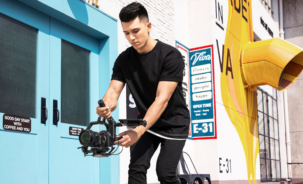 A young man using the Weebill S DSLR gimbal whilst walking down a street