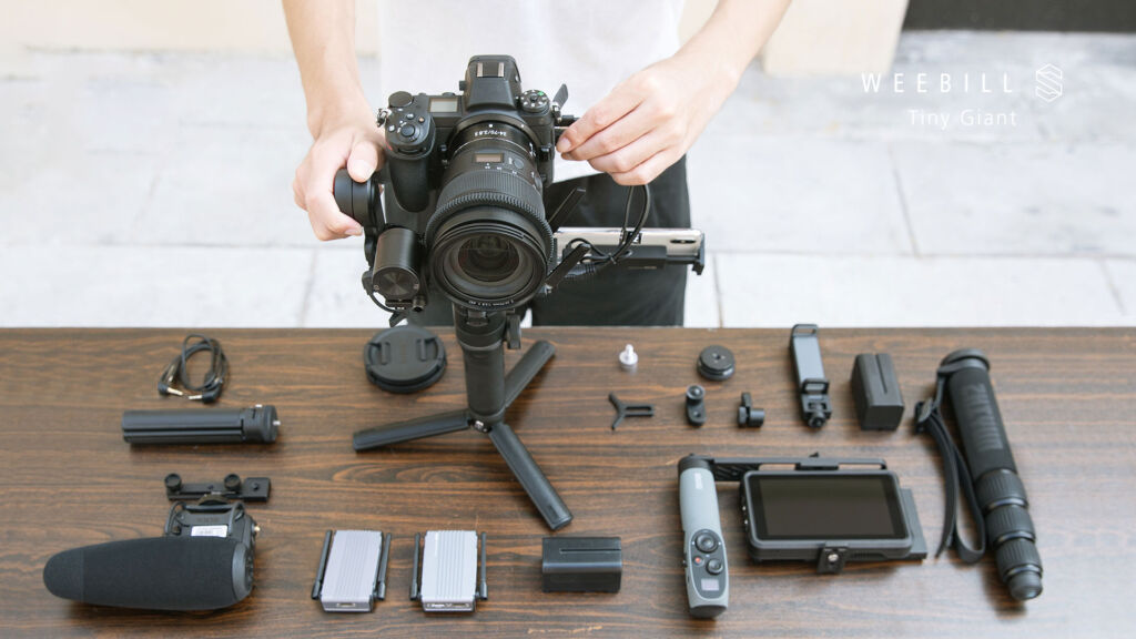 The gimbal places on a table on its tripod with a selection of accessories