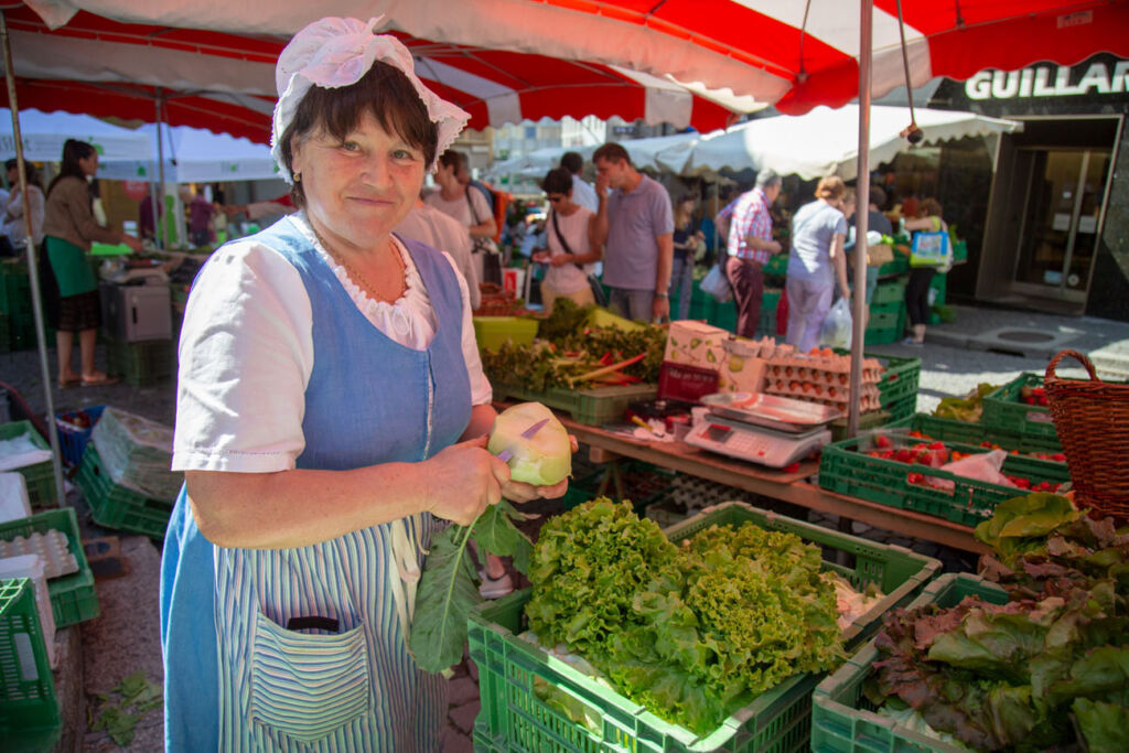 A woman selling local grown produce at a market stall