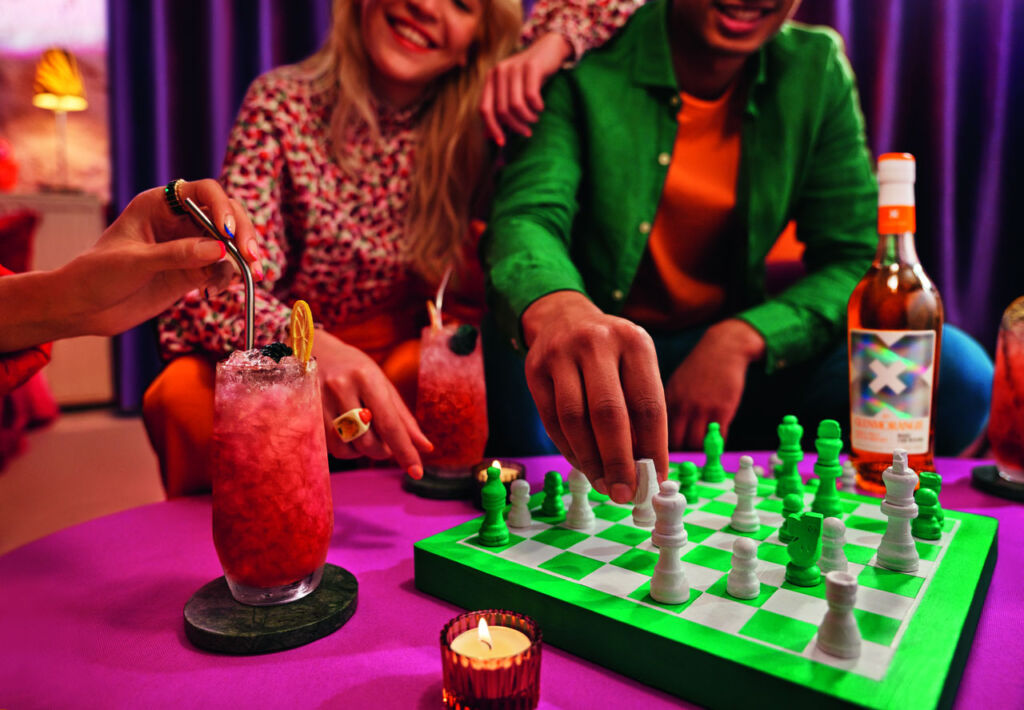 People playing a game of chess while enjoying cocktails made with X by Glenmorangie