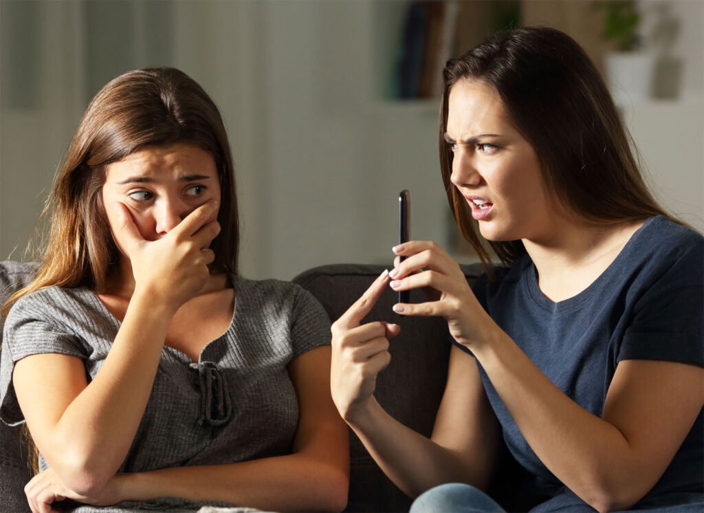 A young woman embarrassing her friend