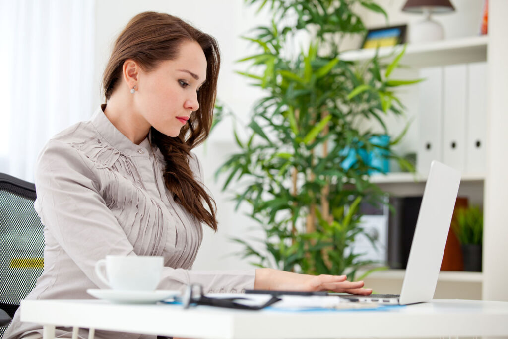 A young woman working from home surrounded by plants