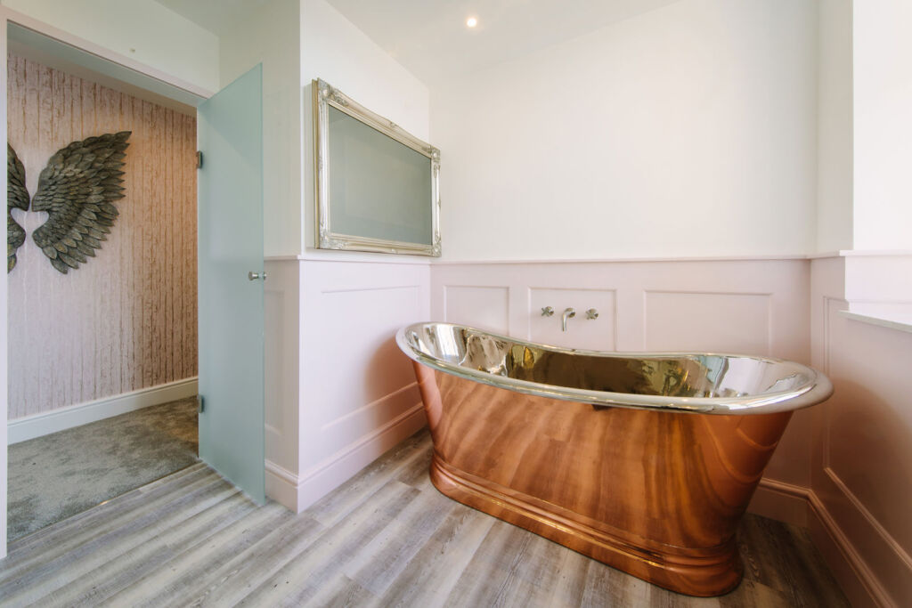 The bathroom with its shiny copper bath in the Parisian Bedroom suite